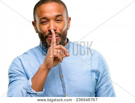 African american man with beard with index finger on lips, ask to be quiet. Silence and secret concept isolated over white background