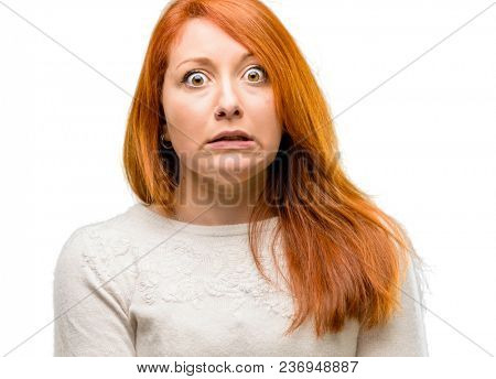 Beautiful young redhead woman nervous and scared biting lips looking camera with impatient expression, pensive isolated over white background