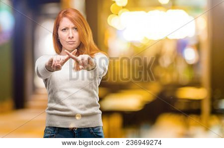 Beautiful young redhead woman annoyed with bad attitude making stop sign with hand, saying no, expressing security, defense or restriction, maybe pushing at night