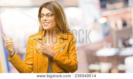 Beautiful young woman pointing away side with fingers at restaurant