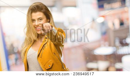 Beautiful young woman pointing to the front with finger at restaurant