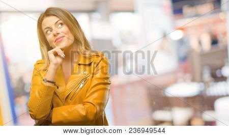 Beautiful young woman thinking and looking up expressing doubt and wonder at restaurant