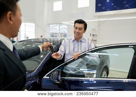 Salesman Giving Car Keys To Happy Customer