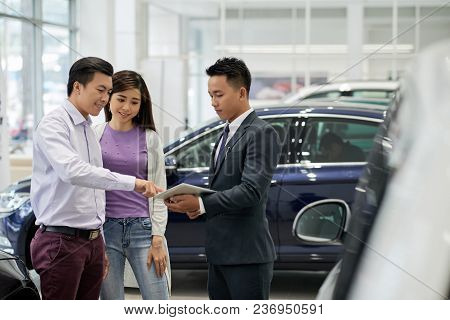 Car Dealership Salesman Showing Information On Tablet Computer To Customers