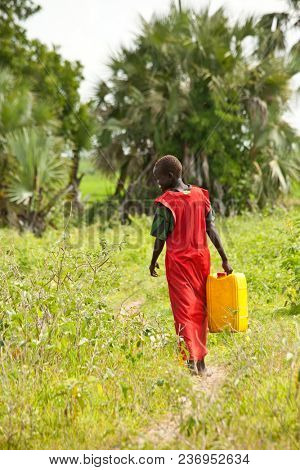MANGALLA, SOUTH SUDAN-JUNE 23, 2012: An unidentified boy carries a water jug to get water from the Nile River near Mangalla, South Sudan.