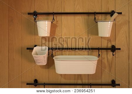 White Hanging Box Shelves On Wooden Background. White Box Hanging On Black Bars.