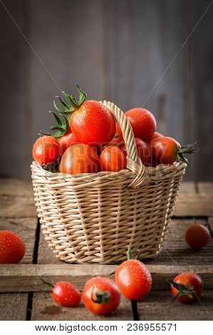 Small Red Cherry Tomatoes  In A Small Wicker Basket  On Wooden Table. Healthy Organic Food. Tomato H