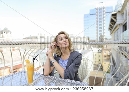 Charming Female Person Drinking Orange Juice At Cafe On Balcony With Cityscape Background. Concept O