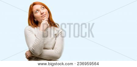 Beautiful young redhead woman thinking and looking up expressing doubt and wonder isolated over blue background