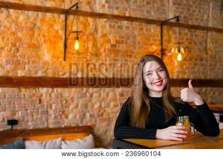 Young Woman Enjoying Nice Atmosphere Of Favorite Coffee House, Smiling Fair-haired Lady Wearing Whit