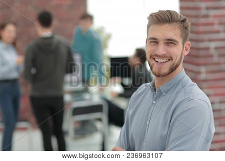 Successful  young business man standing with his colleagues in b