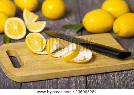 Whole Lemons And Pieces Of Fruit With Peel On Wooden Chopping Board Next To Knife