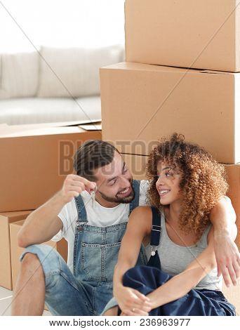Happy new tenants sitting near cardboard boxes