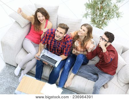 group of friends watching a video on a laptop and laughing