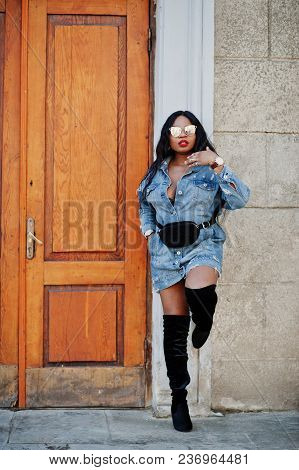 African American Girl In Jeans Dress And Sunglasses Posed On Streets Of City. Black Stylish Model Sh