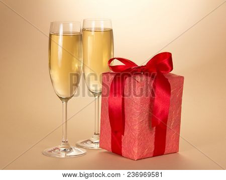 Christmas Gift In Red Box With Bow And Two Glasses Of Champagne, On Beige Background