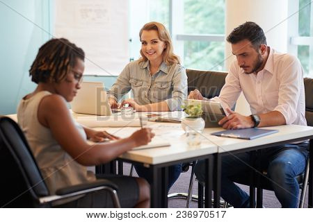 Male And Female Colleagues Gathered Together At Spacious Boardroom And Brainstorming On Their Joint