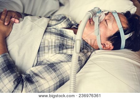 A man sleeping with anti snoring chin strap