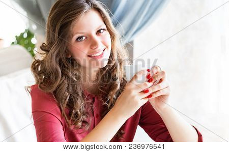 Pleasant Beautiful Young Woman Drinking Hot Coffee In A Cafe