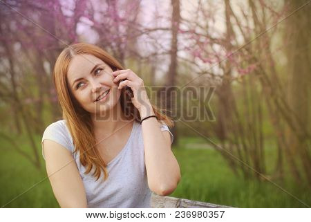 Young Girl Women Talking On A Mobile Phone Green Summer Garden. A Blonde Woman Smiling Till Talking