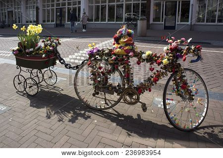 Amsterdam, Holland - 14 April 2018 A Bicycle With A Cart, Decorated With Artificial Flowers And A Ru