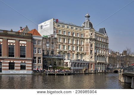 Amsterdam, Holland - 14 April 2018 Canal Dock Cafe And Nh Doelen Hotel View. Netherlands,