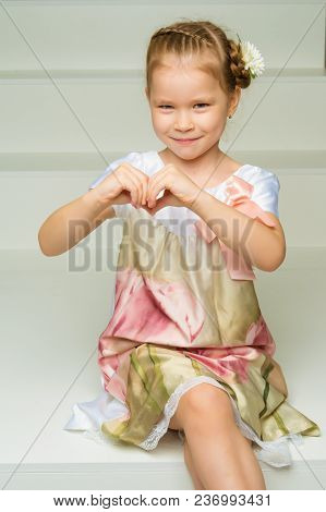 Beautiful Little Girl Shows Heart By Hands. The Concept Of Happy People, Childhood.