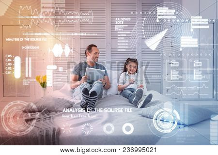 New Tablets. Cheerful Man Relaxing On A Comfortable Big Bed And Holding A Tablet While His Daughter