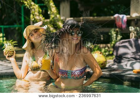 Attractive Smiling Girls In Bikinis Holding Pineapple And Cocktail In Swimming Pool