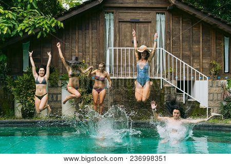 Beautiful Young Women In Swimwear Jumping In Swimming Pool At Tropical Resort