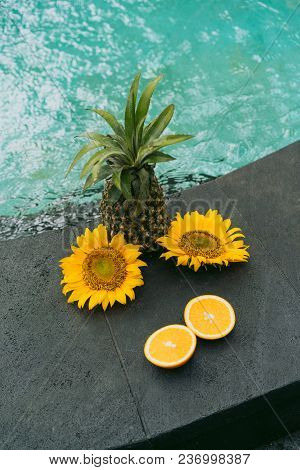 Close-up View Of Pineapple, Sliced Orange And Beautiful Yellow Flowers At Swimming Pool