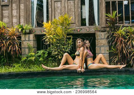 Beautiful Young Women In Swimwear Resting Near Swimming Pool And Looking At Camera
