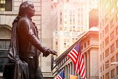 Wall Street in New York City at sunset with the statue of George Washington at the Federal Hall poster