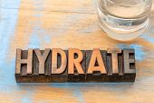 hydrate advice - word abstract in vintage letterpress wood type with a glass of water poster