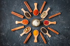 Various Indian Spices In Wooden Spoons, Seeds, Herbs On Dark Stone Table. Colorful Spices, Top View.
