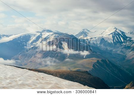 Atmospheric Alpine Landscape With Snow On Peak And Big Snowy Mountains. Low Clouds Above Valley Amon