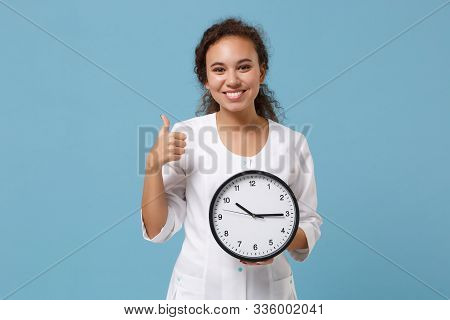Smiling African American Female Doctor Woman In White Medical Gown Hold Clock Showing Thumb Up Isola