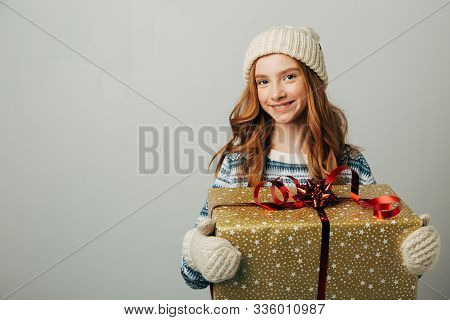 A Teenager In A Knitted Hat, Sweater And Gloves Is Smiling. A Girl Hugs Her Christmas Present From H
