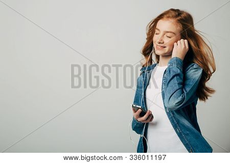 Red-haired Girl Listens To Music In Small Headphones. She Really Loves The Work Of One Artist. A Tee