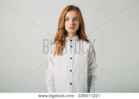 A Young Red-haired Girl Is Looking At The Camera. A Girl With A Worried Video Is Trying To Draw Your
