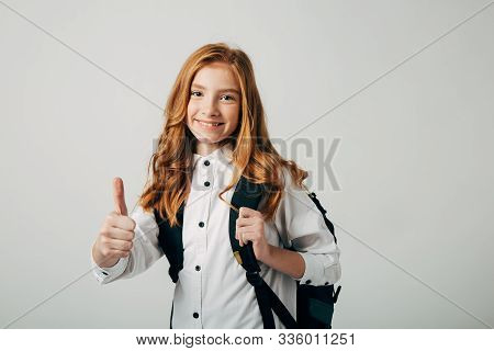 A Young Red-haired Girl Goes To School. Schoolgirl Shows Thumb Up And Goes To Study Lessons. A Cheer