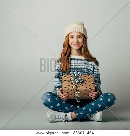 Teen In A Knitted Hat And Sweater Bought A Christmas Present For Parents At A Low Price. The Girl Is