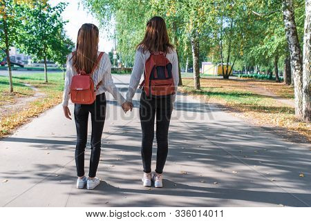 Two Teenage Girls Walk In Summer In Park, Walk After School And College, Hold Hands, Best Friends Re