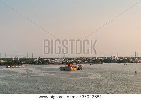 Phuoc Khanh, Vietnam - March 13, 2019: Long Tau River At Sunset. Wide Shot On Town With 2 Barges Alo