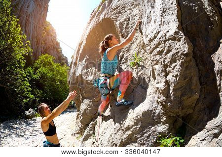 Two Girls Are Trained In Natural Relief. Rock Climber Climbs A Rock. Woman Insures A Friend. Mountai