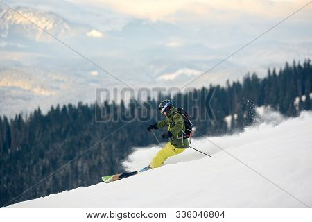 Skier Descending At High Speed From Snow-covered Mountain Peak. Proficient Skier With Backpack. Extr
