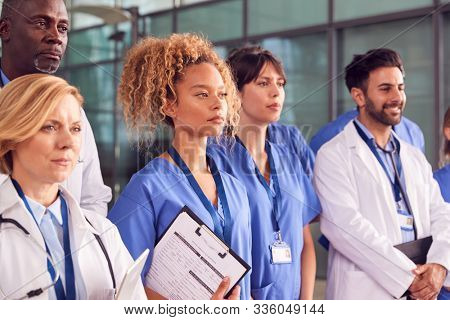 Serious Medical Team Standing In Modern Hospital Building