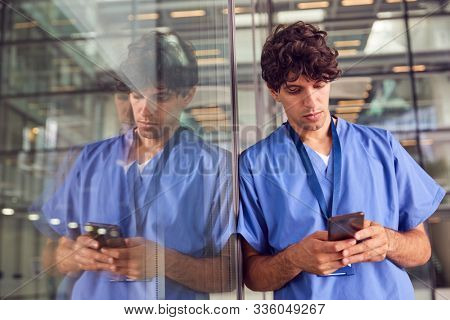 Young Male Doctor Wearing Scrubs Using Mobile Phone Leaning Against Wall In Modern Hospital Building