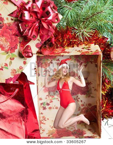 The girl in a New Year's cap in a gift box under a fir-tree
