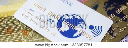 Focus On Credit Card With Bank And Card Holder Name. Bankcard Lying On Banknotes. World Map Painting